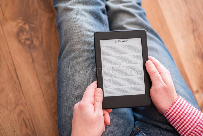 Leyendo una novela en lector del ebook en casa fotos de archivo