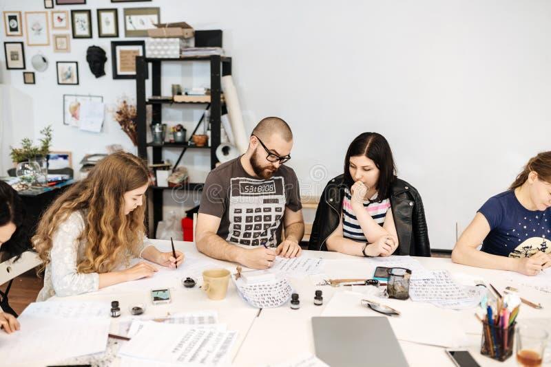 Lezing en opleiding in kalligrafiebureau voor een groep mensen stock afbeeldingen