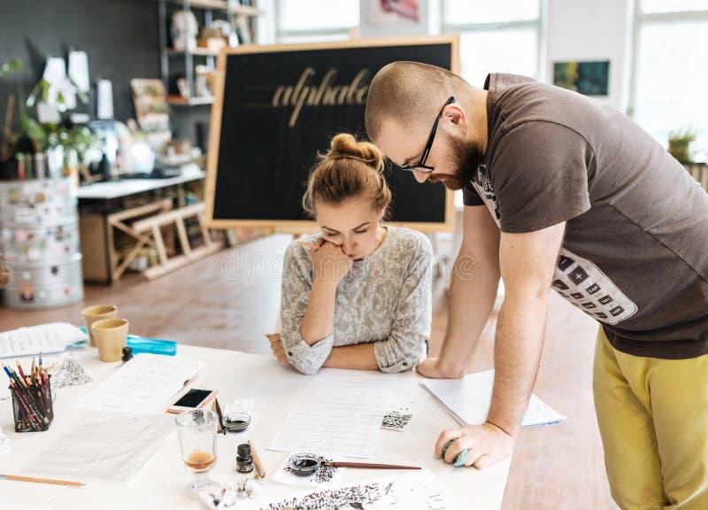 Lezing en opleiding in kalligrafiebureau voor een groep mensen stock fotografie