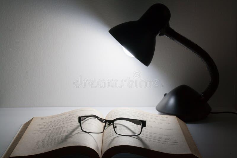 Lezingsglazen die bovenop open boek naast nachtlamp rusten stock foto
