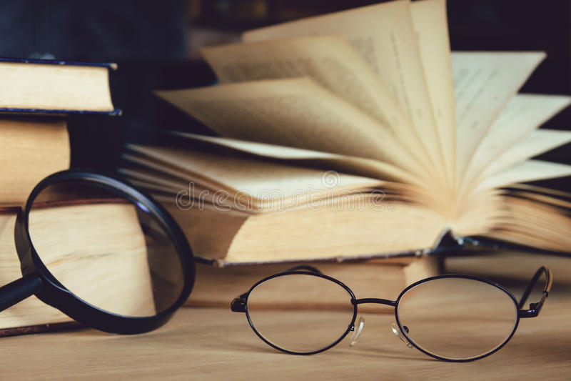 Lezingsglazen en vergrootglas met oldsboek op lijst stock foto's