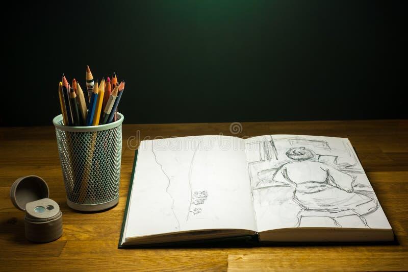 Lezione del disegno dello Sketchbook sulla tavola con i pastelli e le matite colorate fotografia stock libera da diritti