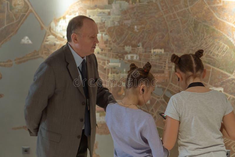Lezione di geografia a due ragazze programma interattivo Un maestro di scuola più anziano spiega una lezione di geografia a due r immagini stock