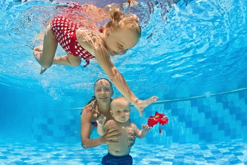Lezione di nuoto subacqueo del bambino con l'istruttore nello stagno fotografia stock libera da diritti