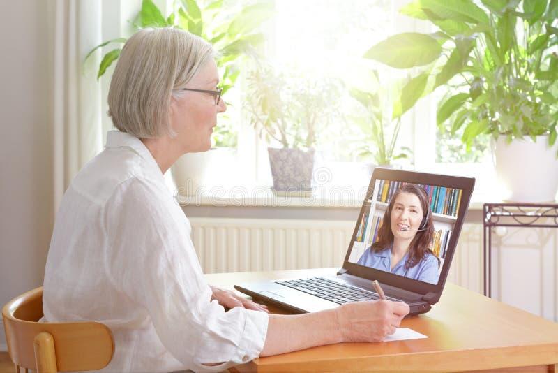 Lezione online del computer portatile senior della donna fotografia stock