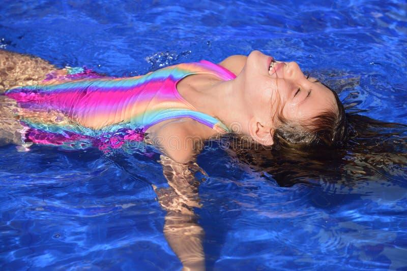 Lezioni di nuoto: Bambino che impara galleggiare fotografia stock