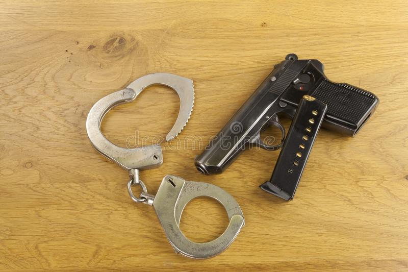 Lfirearm que miente en la tabla, policía del metal esposa foto de archivo libre de regalías