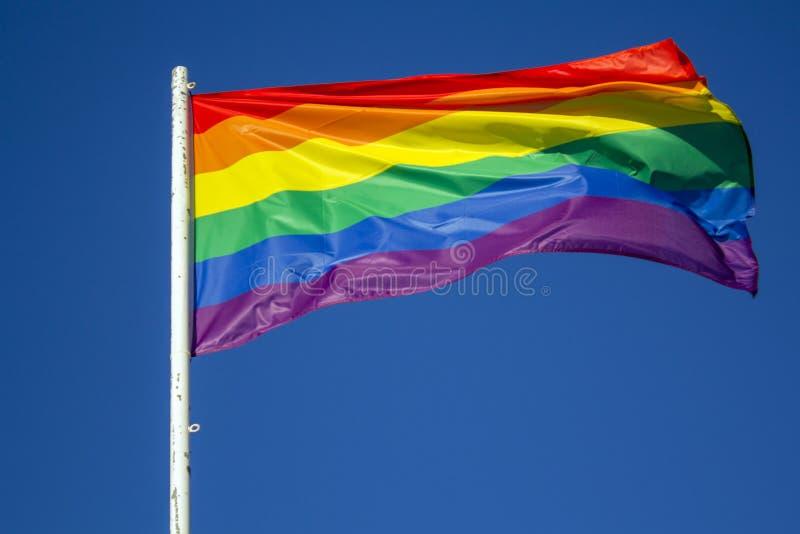 LGBT彩虹反对蓝天的自豪感旗子 免版税库存照片