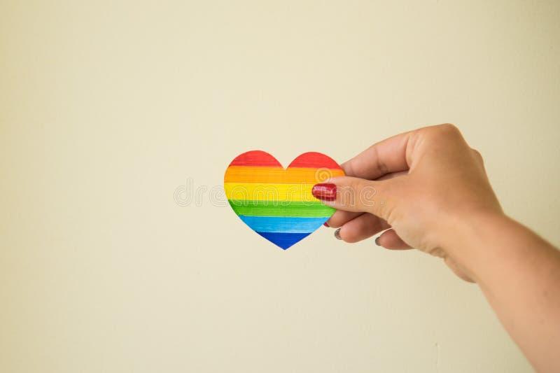 LGBT概念妇女递举行心脏彩虹颜色 LGBT 库存图片