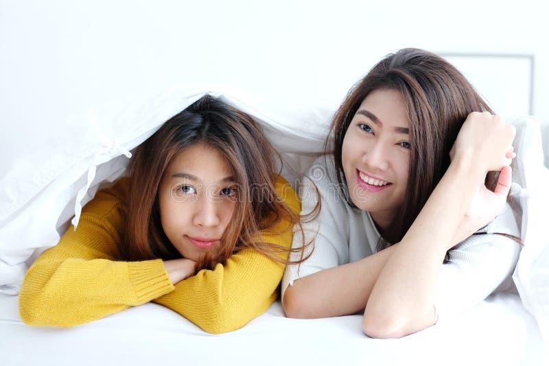 lgbt,一起在和微笑在白色床上的年轻逗人喜爱的亚洲女同性恋者早晨
