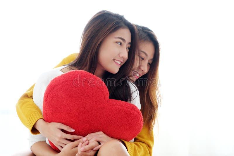 LGBT, huging和拿着红色心脏shap的年轻逗人喜爱的亚洲女同性恋者 免版税图库摄影