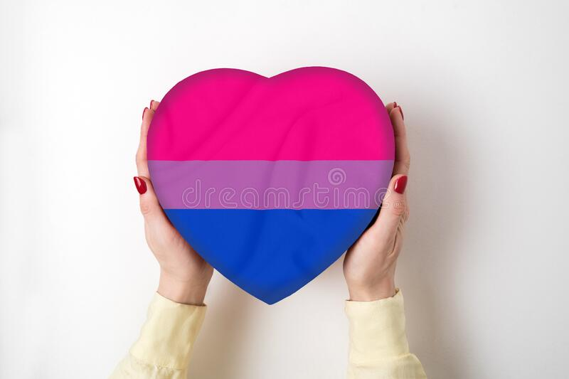 LGBT bisexual pride flag on a heart shape box in female hands. Pride symbol. Top view.  stock images