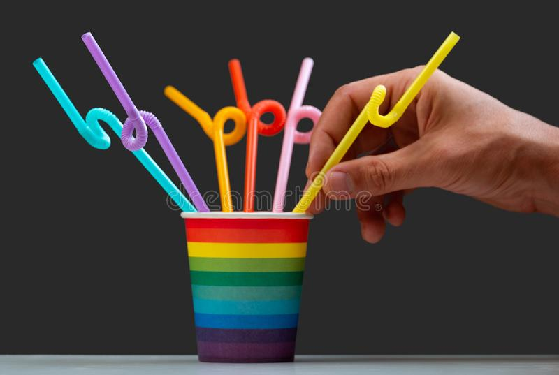 LGBT color cup with multi-colored cocktail tubes on a gray background. Male hand holds a straw for drinks. The concept of stock photos