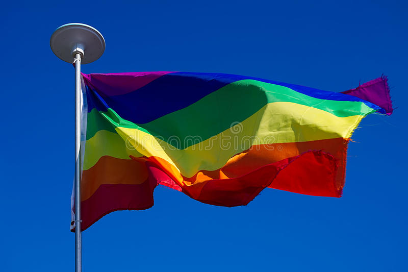 LGBT flag waving on wind on blue sky background. Rainbow flag waving on wind on blue sky background stock photo