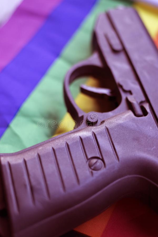 LGBT gay pistol gun. Automatic pistol handgun with gay lesbian LGBT homosexual pride rights flag colors royalty free stock images