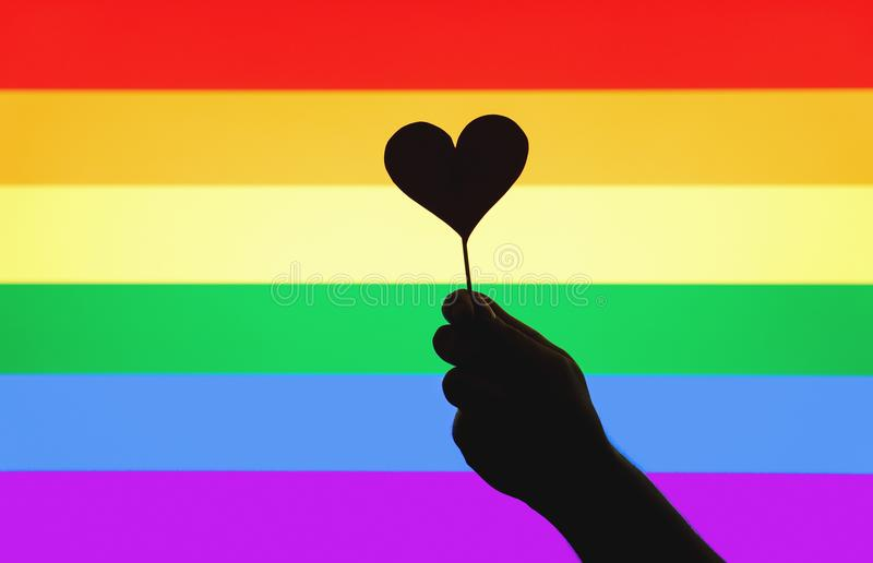 LGBT, gay pride, sexual minority, homosexuality and equal rights. Concept. Silhouette hand holding cardboard heart on a wooden stick against rainbow flag stock photo