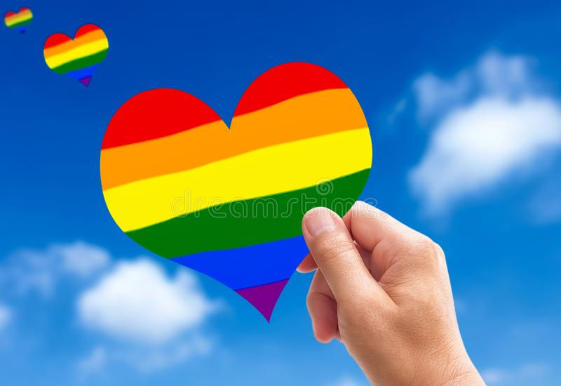 LGBT heart. Man hands holding a heart-shaped bright Rainbow colors from the sky stock photos