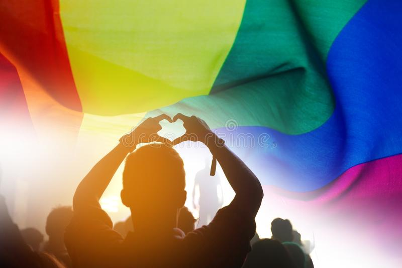 LGBT. Pride community at a parade with hands raised and the LGBT flag royalty free stock image