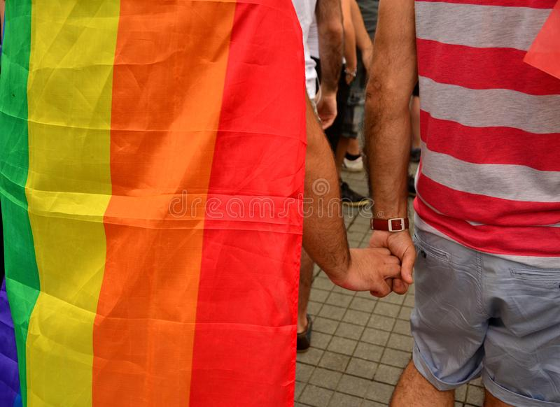 LGBT PRIDE Parade walk hand in hand. Two male LGBT men holding hands walk on the street. On the back of one of them is the flag of the LGBT population. Only stock images