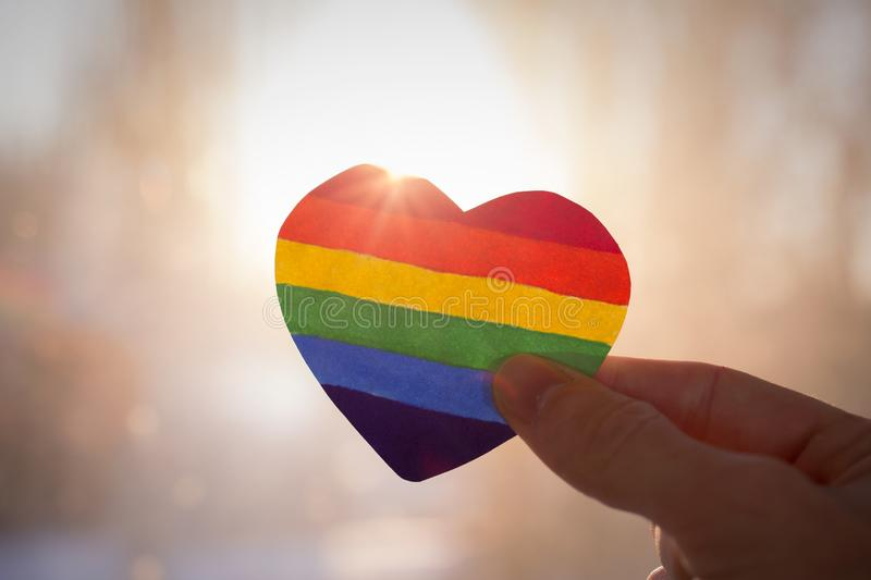 Lgbt rights concept. Hand holds a heart painted like a LGBT flag, silhouetted against sun stock image