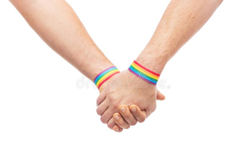 Hands of couple with gay pride rainbow wristbands. Lgbt, same-sex relationships and homosexual concept - close up of male couple wearing gay pride rainbow stock photography