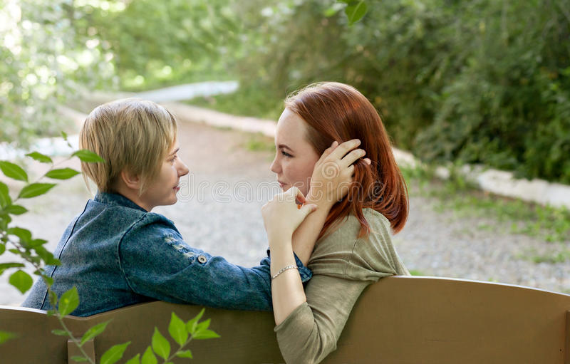 LGBT women. Young lesbian couple walking in the park together. Delicate relationship. Selective focus. LGBT women. Young lesbian couple walking in the park royalty free stock image