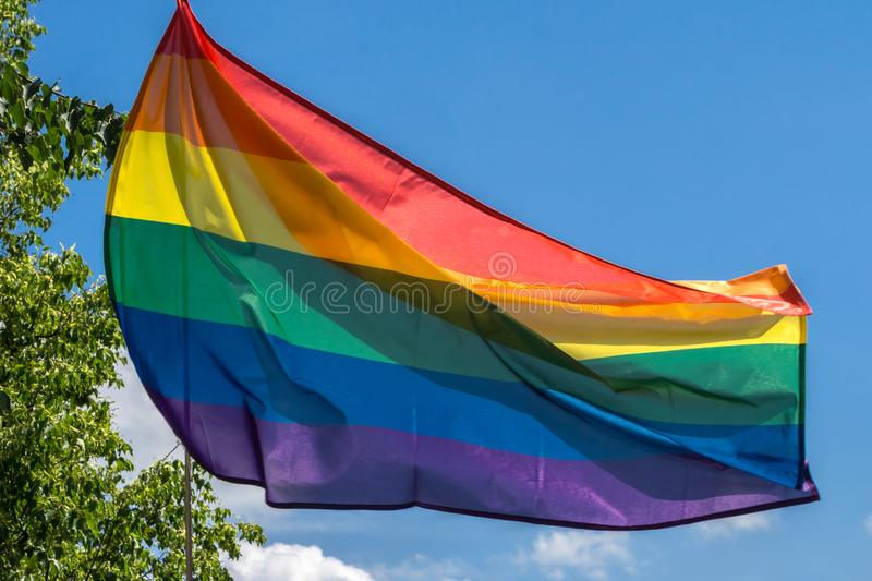 LGBTQI or LGBT rainbow pride flag in breeze on blue sky background stock photo