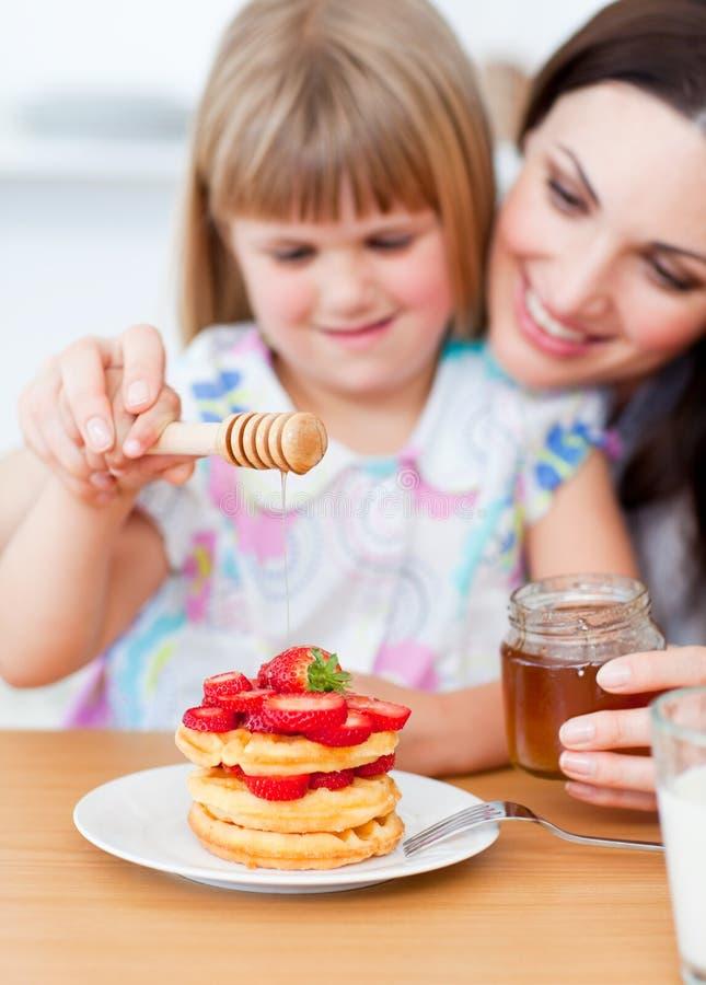 Lgirl mignon et sa mère mettant le miel sur des gaufres image stock