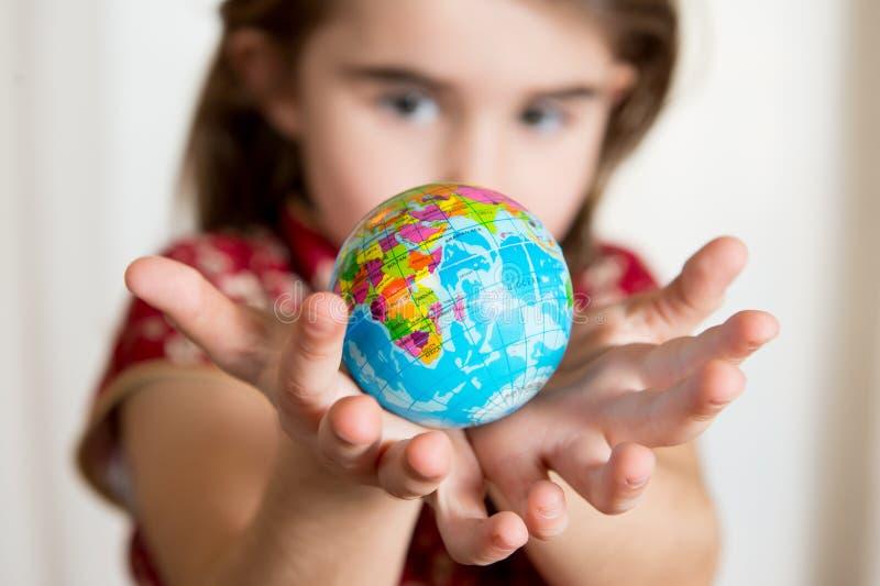 Lgirl mignon tenant peu de globe du monde sur ses mains images stock
