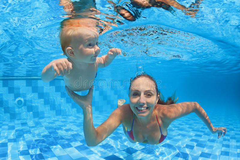 Lição da natação da criança - bebê com o mergulho do moher subaquático na associação fotos de stock