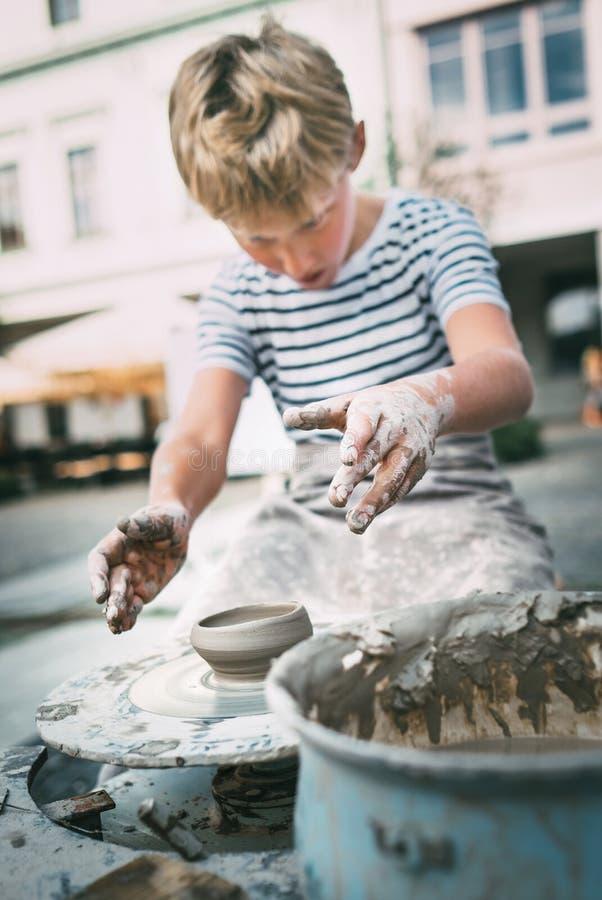 Lição tradicional do ofício: tentativa do menino para fazer uma bacia da cerâmica fotos de stock
