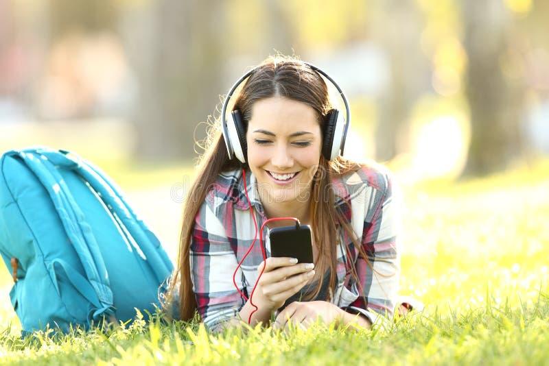 Lições audio de escuta do estudante feliz na linha foto de stock royalty free
