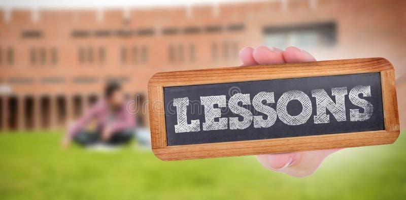 Lições contra os estudantes que usam o portátil no gramado contra a construção da faculdade fotos de stock royalty free