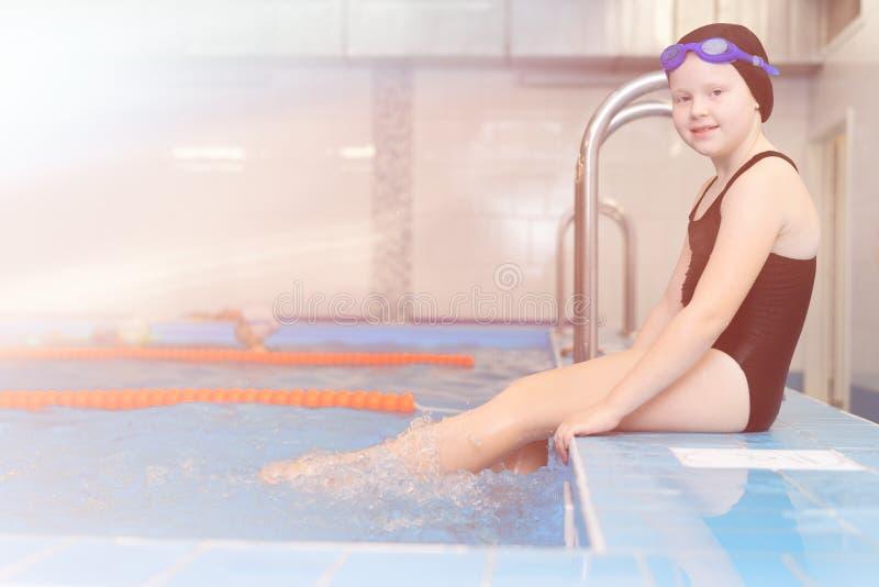 Lições da natação para as crianças na associação - retrato de uma menina branco-descascada bonita em um maiô e em um tampão da na imagem de stock royalty free