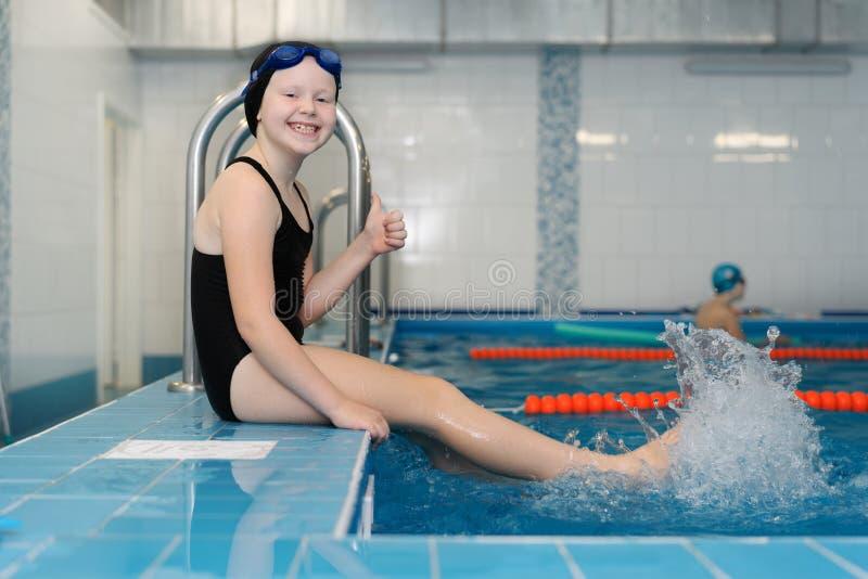 Lições da natação para as crianças na associação - retrato de uma menina branco-descascada bonita em um maiô e em um tampão da na foto de stock royalty free