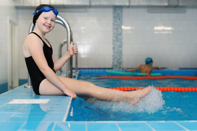 Lições da natação para crianças na associação - a menina justo-descascada bonita nada na água fotografia de stock royalty free