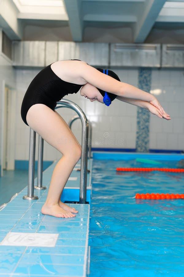 Lições da natação para crianças na associação - a menina justo-descascada bonita nada na água foto de stock royalty free