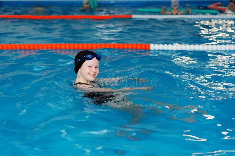 Lições da natação para crianças na associação - a menina justo-descascada bonita nada na água fotos de stock royalty free