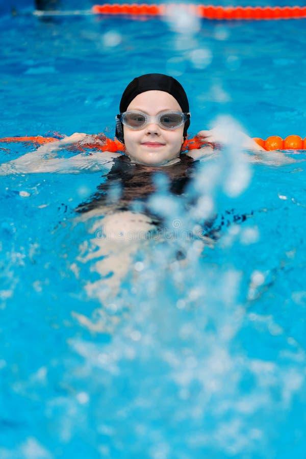 Lições da natação para crianças na associação - a menina justo-descascada bonita nada na água fotos de stock