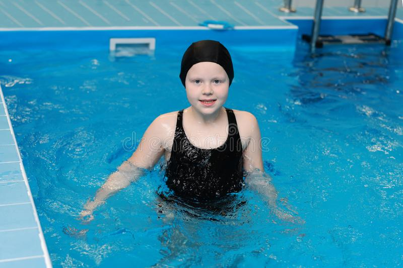 Lições da natação para crianças na associação - a menina justo-descascada bonita nada na água imagens de stock