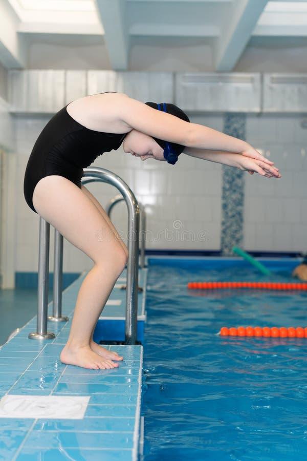 Lições da natação para crianças na associação - a menina justo-descascada bonita nada na água imagem de stock royalty free