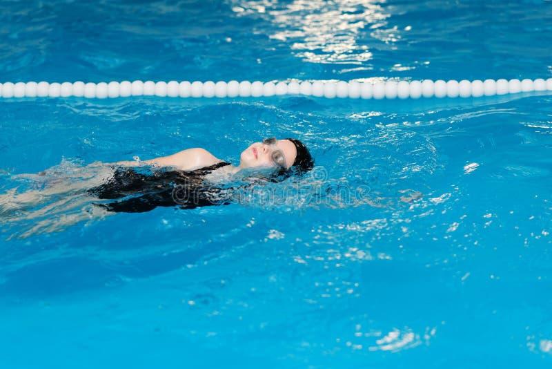 Lições da natação para crianças na associação - a menina justo-descascada bonita nada na água imagem de stock