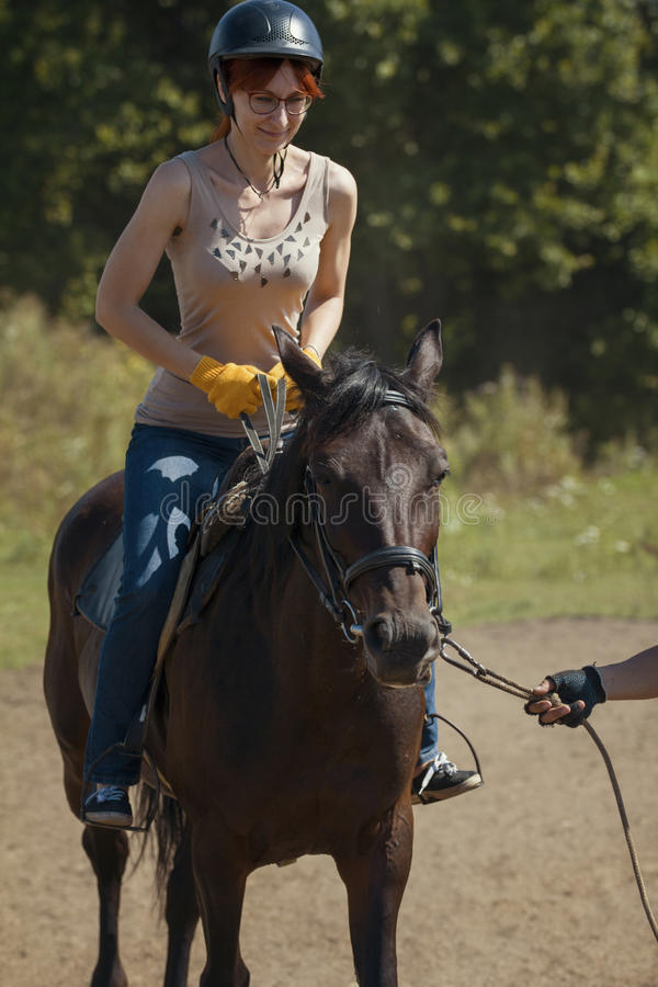 Lições de equitação - jovem mulher que monta um cavalo imagem de stock