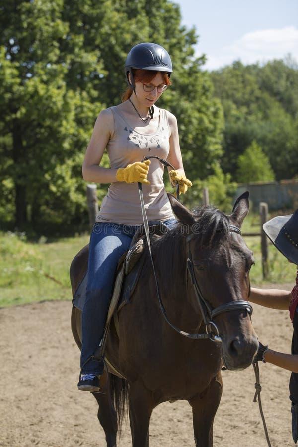Lições de equitação - jovem mulher que monta um cavalo imagens de stock