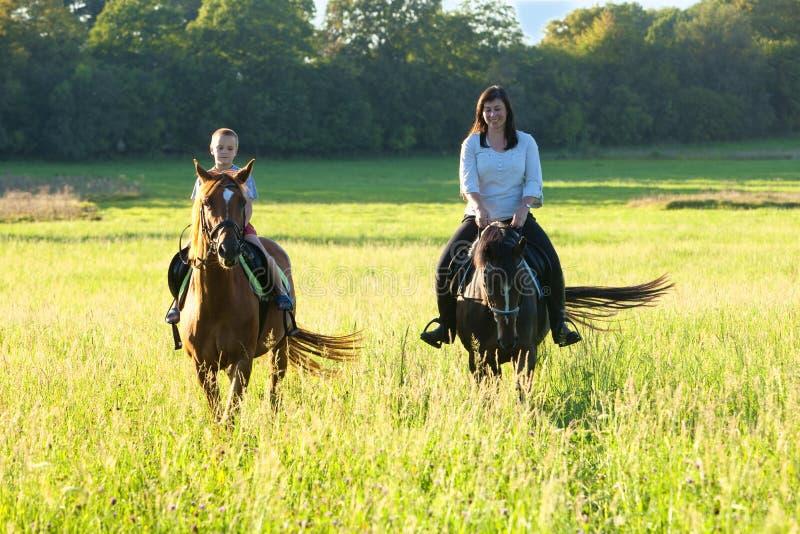 Lições de equitação - mulher que conduz um cavalo com um menino em S foto de stock