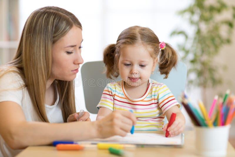 Lições do desenho da menina do professor e da criança de jardim de infância na escola foto de stock royalty free