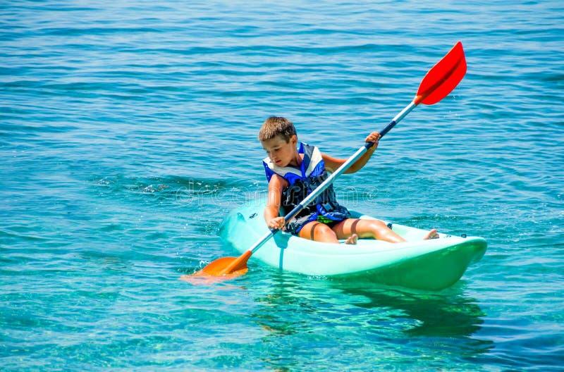 Lições Kayaking Menino com o terno da boia de vida no duri das lições do caiaque imagem de stock royalty free