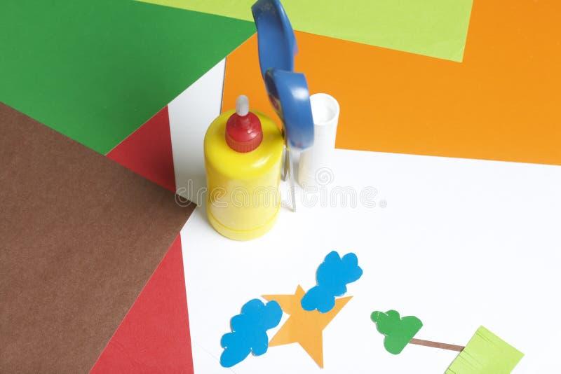 Lições no applique Artigos necessários: a colagem, o papel colorido e as tesouras encontram-se na superfície branca da tabela Cor imagens de stock