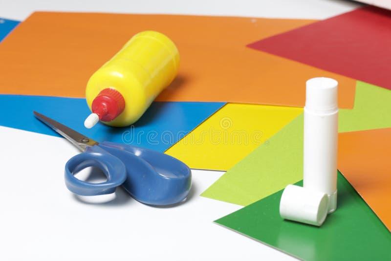 Lições no applique Artigos necessários: a colagem, o papel colorido e as tesouras encontram-se na superfície branca da tabela fotos de stock royalty free