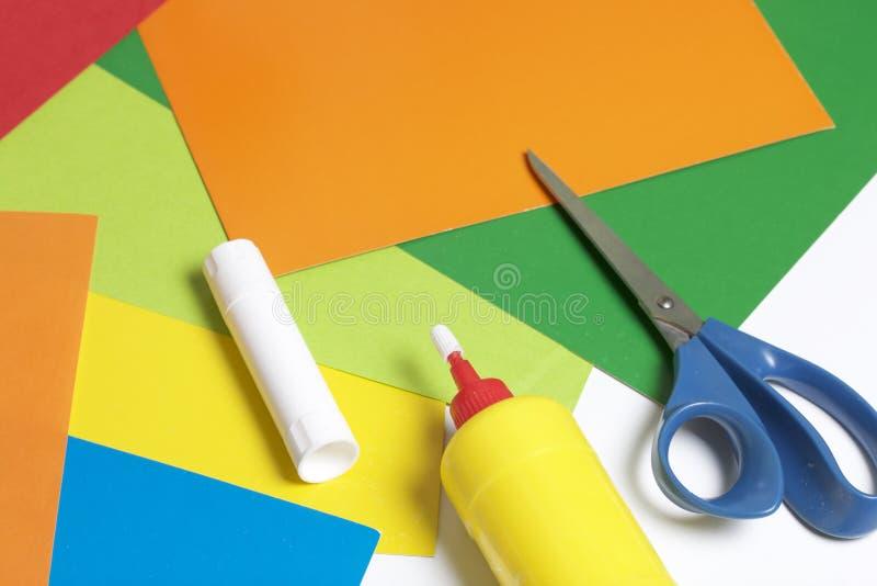 Lições no applique Artigos necessários: a colagem, o papel colorido e as tesouras encontram-se na superfície branca da tabela imagens de stock royalty free